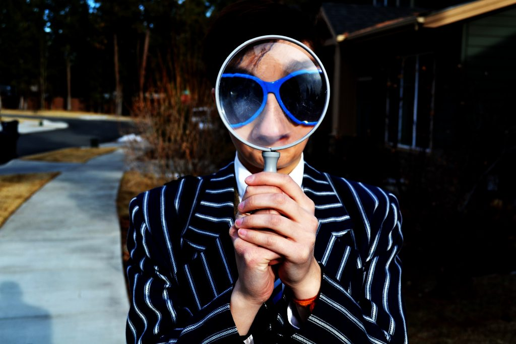 A man wearing sunglasses seeing through magnifying glass.